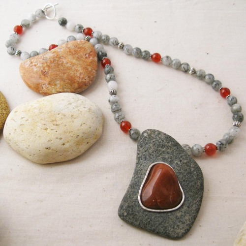 Red quartzite set within grey granite in a silver setting.  The beads are rutile quartz and carnelian.