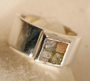 4 colored rough diamonds set in a silver wedding band
