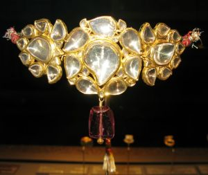 A bazuband to be worn on the front of a princess, made of large diamonds set in gold with a spinel drop in front.