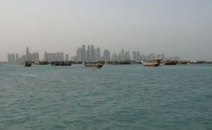Dhow harbor with ancient boats and modern high rises