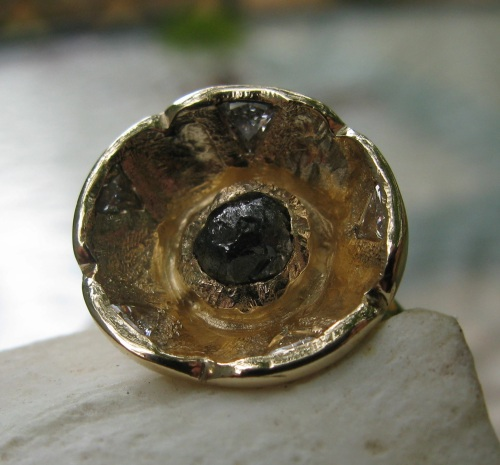 Gold ring with central black diamond in the rough and 5 trillion diamonds