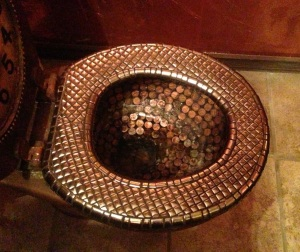Toilet bowl tiled with copper pennies