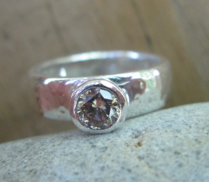 Champagne diamond (0.6 ct) with lots of brilliance in a simple hammered silver ring.  I love the simplicity.